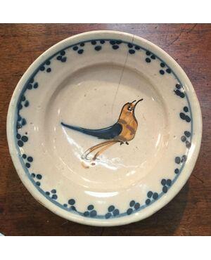 Piatto in maiolica decorato con un uccellino stilizzato.Manifattura Grosso di Albisola.