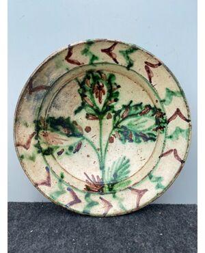 Piatto in ceramica ingobbiato a decoro 'popolaresco' con elementi vegetali stilizzati.'Verso' parzialmente invetriato.Calabria.