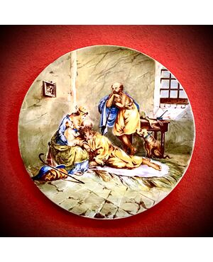 Piatto in maiolica a decoro istoriato con scena 'Susanna e i vecchioni'.Manifattura Ferniani,Faenza.