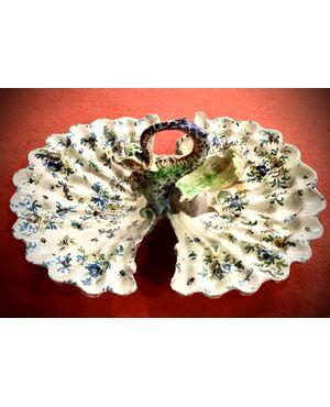 Centrotavola in maiolica a forma di conchiglia bivalve con presa a drago e decoro a fiori e insetti.Angelo Minghetti,Bologna.