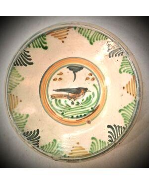 Piatto in maiolica con motivi vegetali stilizzati sulla tesa e uccellino nell'umbone.Manifattura di Montelupo.