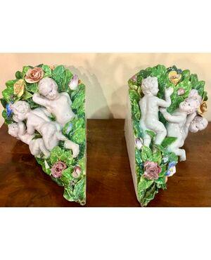 coppia di vasi applique angolari decorati con putti e fiori in rilievo. manifattura Minghetti di Bologna.